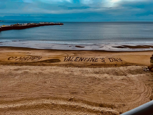 Beach with Happy Valentine's Day written in the sand